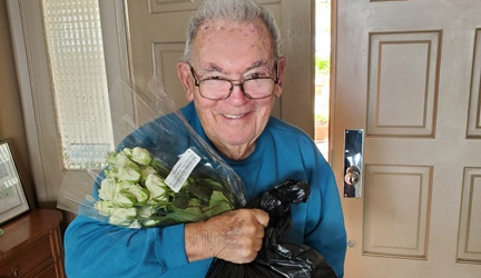 Senior receiving meal and flowers from Torrance-South Bay YMCA
